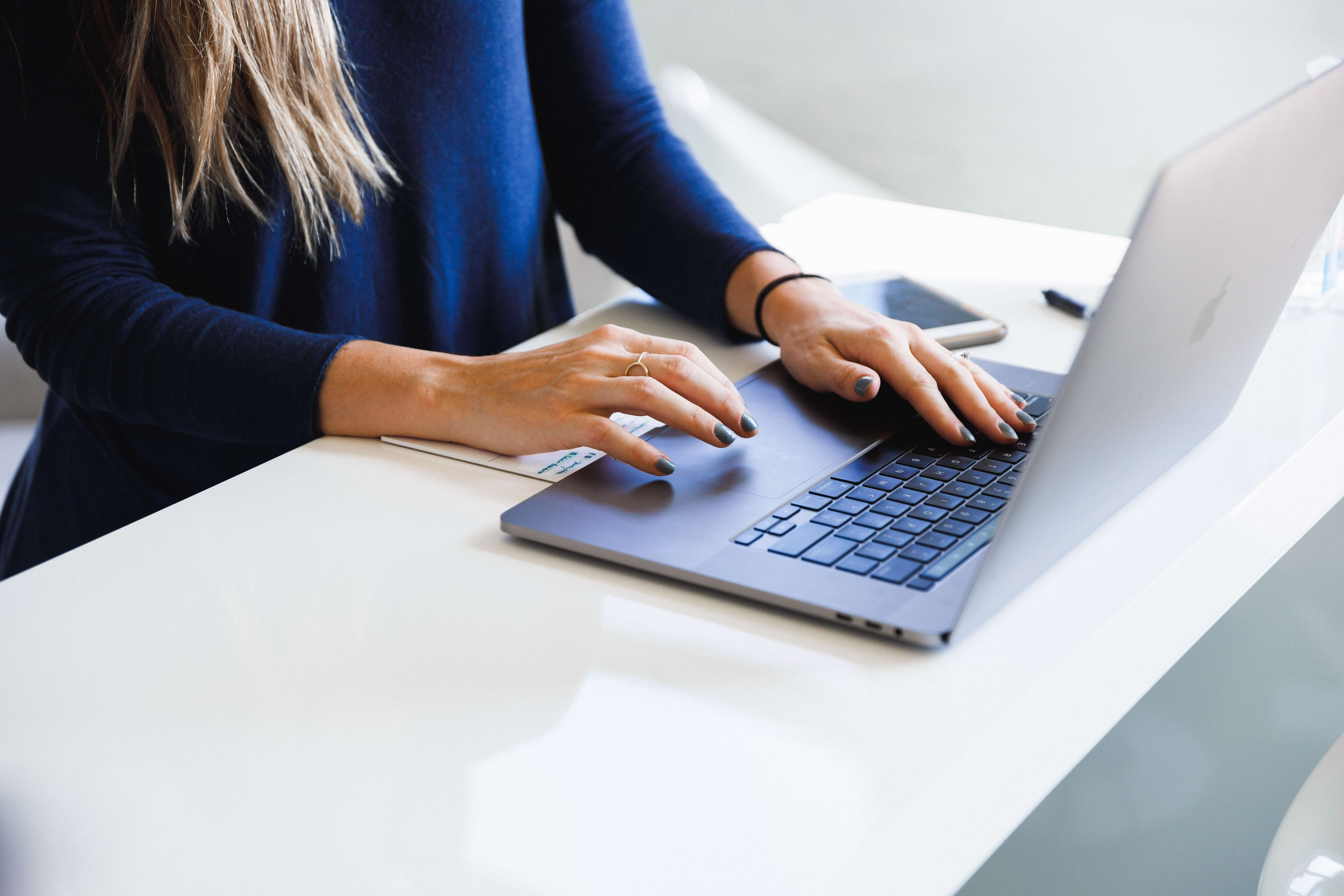 Woman sitting a desk typing on a MacBook.